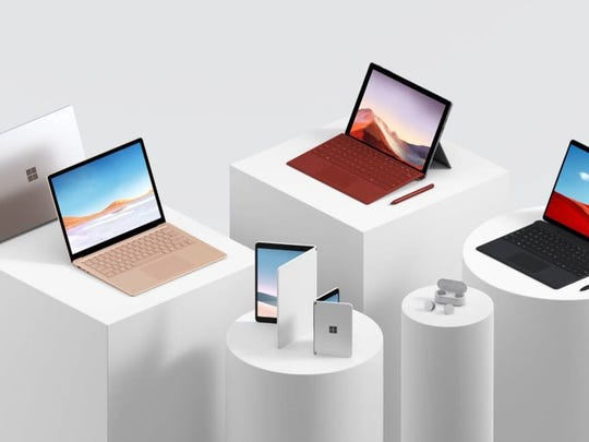 In the foreground, left to right, are Microsoft's new Surface Neo, Surface Duo, and Surface Earbuds. At rear, left to right, are the Surface Laptop 3, Surface Pro 7, and Surface Pro X.