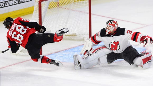 Ottawa Senators left wing Mike Hoffman (68) flies through the air as he attempts to score on New Jersey Devils goalie Cory Schneider during the first period of an NHL hockey game, Thursday, Oct. 19, 2017 in Ottawa, Ontario. (Sean Kilpatrick/The Canadian Press via AP)