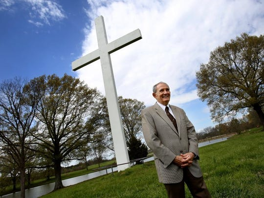 Buddy Runnels stands in front of a 50-foot-tall cross