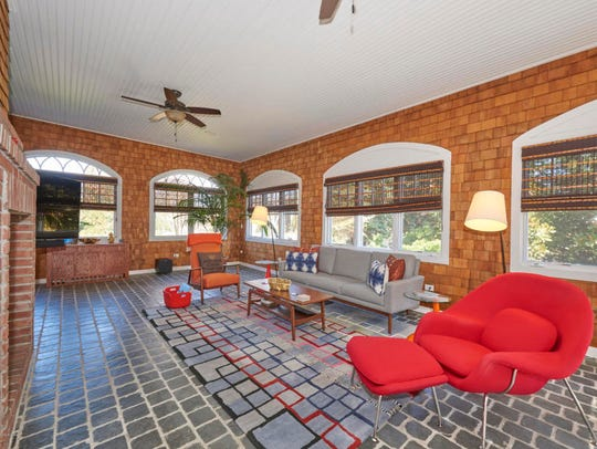 The sunroom features tile flooring and customized windows.
