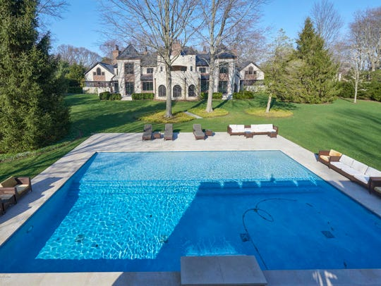 The home features an in-ground saltwater pool surrounded by professional landscaping.