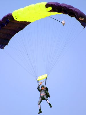 Tommy Fergerson soars in the sky above the Fremont County Airport during his 1,000th parachute jump. The skydiver has prevailed in reaching the milestone after two accidents that nearly cost him his life.