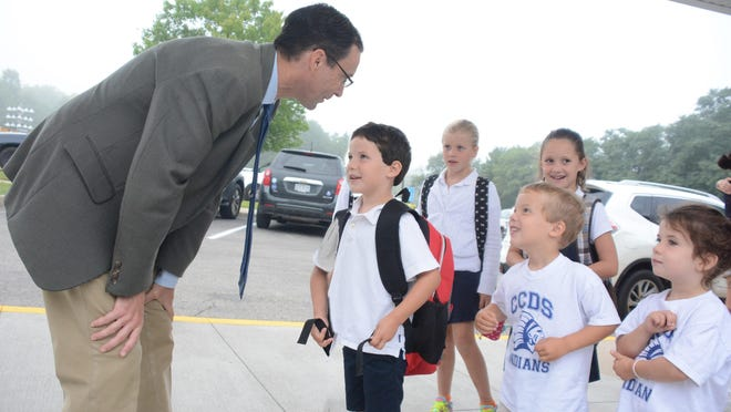 Tony Jaccaci, the new head of school at CCDS, greets Lower School students as they arrive on the first day. Front, from left, are kindergartner Liam Steele of Loveland and his 4-year-old siblings, Aidan and Emma, who are aspiring CCDS students. In back are second-graders Sophie Parlin, left, of Indian Hill, and Addy Steele of Loveland.