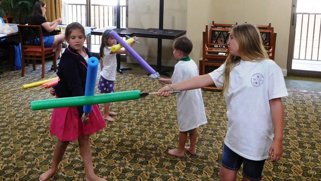 A fight scene with pool noodle swords.