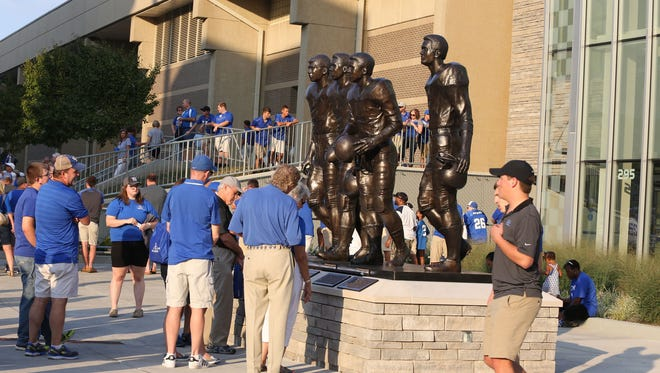 Fans look at the statue of Nate Northington, Greg Page, Wilbur Hackett and Houston Hogg outside of Commonwealth Stadium in Lexington on Saturday. The four players broke the color barrier at the University of Kentucky and the Southeastern Conference in 1967-68.