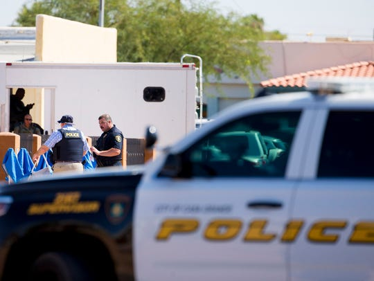 Law-enforcement officers investigate the deaths of