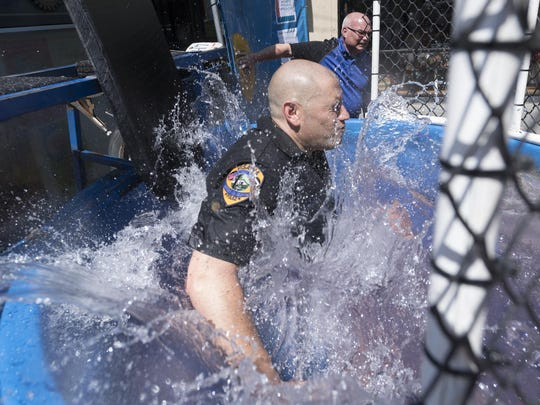 Visalia Police Chief Jason Salazar takes a plunge (with a little help from Mayor Steve Nelsen) in the dunk tank Saturday on Main Street to benefit the American Cancer Society on Saturday, September 10, 2016.