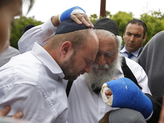 Rabbi Yisroel Goldstein, center, meets with members of the congregation of Chabad of Poway the day after a deadly shooting took place there, on Sunday, April 28, 2019 in Poway, Calif. Goldstein was shot and lost a finger on his right hand. (K.C. Alfred/San Diego Union-Tribune/TNS)