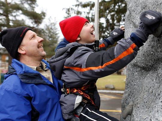 Brian Krieger helps his son Ethan, 10, climb a temporary rock wall at Potter Park in Fairport on Saturday during the Operation Potter Patriot event.