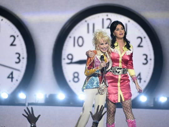Dolly Parton, left, and Katy Perry embrace after performing