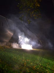 A downed power line burns on the front lawn of a home