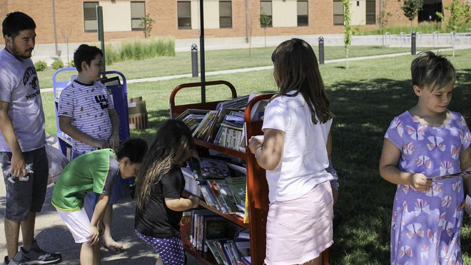 Children look through new and gently used  books at the Salina Area United Way Raising Active Wild Readers (RAWR) program at Salina Central High School. The Salina Area United Way was able to delivered 2,030 children's books to young readers this year.