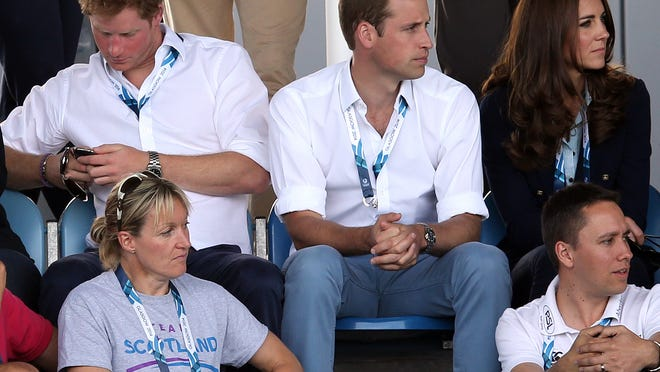 Prince Harry, at the Commonwealth Games in Scotland with Prince William and Duchess Kate on July 28, checks his phone.
