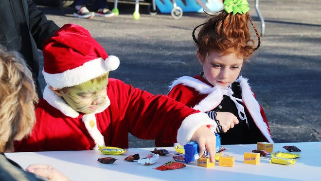 The Grinch picks up some candy while Cindy Lou Who watches Saturday. They were just two of more than 250 children who attended the Trunk-or-Treat event host by the Chenoa Baptist Church.