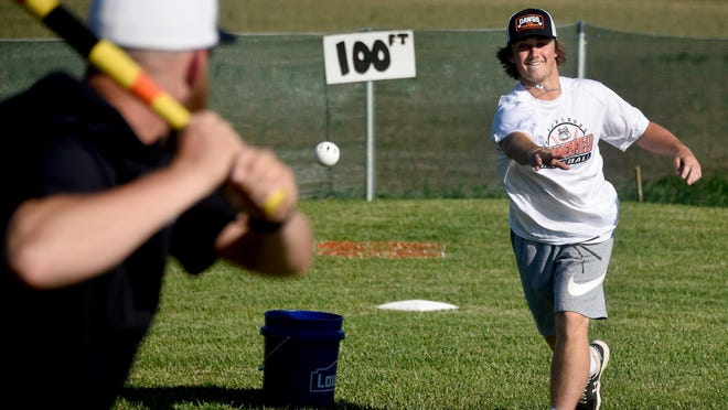 Brock Olmstead pitches a wiffle ball to Summerfield baseball coach Travis Pant.