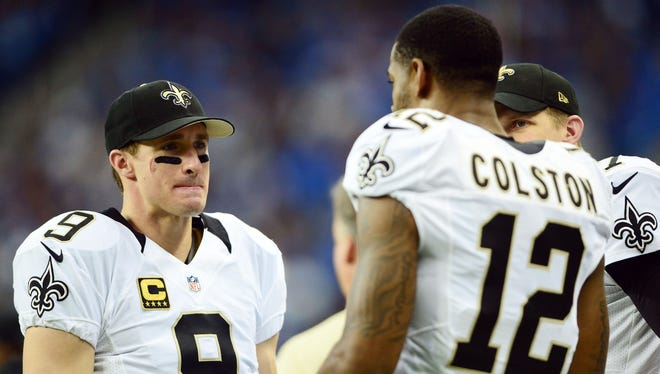 Oct 19, 2014; Detroit, MI, USA; New Orleans Saints quarterback Drew Brees (9) talks with wide receiver Marques Colston (12) on the sidelines during the first quarter against the Detroit Lions at Ford Field.