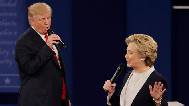 In this Sunday, Oct. 9, 2016, file photo, Republican presidential nominee Donald Trump and Democratic presidential nominee Hillary Clinton speak during the second presidential debate at Washington University in St. Louis. The contentiousness of the presidential election is spilling into some workplaces. And even when there's no rancor, more time is spent on election chatter than in the past. Rather than try to control what people are saying, owners should focus on whether the work is getting done in an atmosphere that's not hostile.