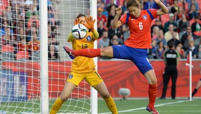 Korea goalkeeper Kim Jungmi and defender Hwang Boram defend the net against a shot by Spain midfielder Marta Corredera (not pictured) in a Group E soccer match in the 2015 FIFA women's World Cup at Lansdowne Stadium.