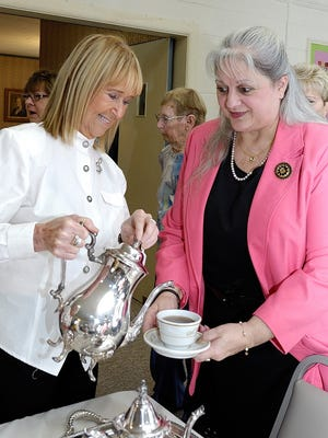 Judy Crowe (left), a past president of the Millville Woman's Club, pours tea for new member EllenBeth Nappen at the club's Thanksgiving Tea. The club's chorus provided entertainment.