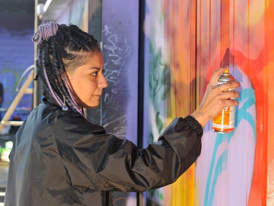Artist lady mist sprays in some color during the Queens