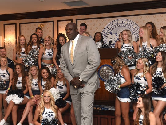 Former basketball player Shaquille O'Neal does a quick pose with the Nevada cheer team as he arrives at the Governor's Mansion as the quest speaker at the 50th annual Governor's Dinner in Carson City on July 12, 2018.