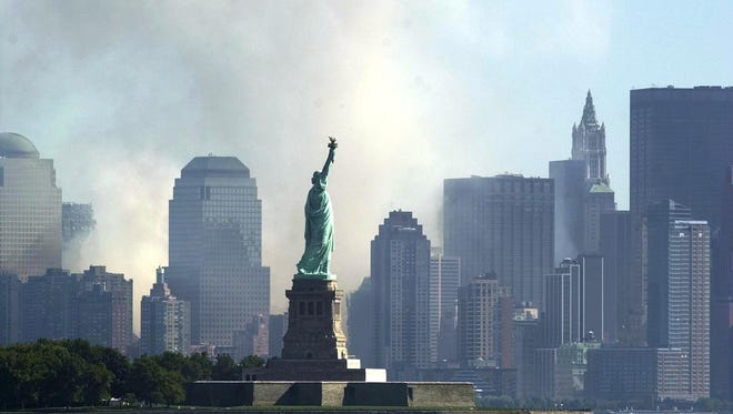 This file photo taken on September 12, 2001, shows  smoke and ash from the destroyed World Trade Center rise over the southern end of New York City's Manhattan behind the Statue of Liberty as seen from Jersey City, New Jersey.