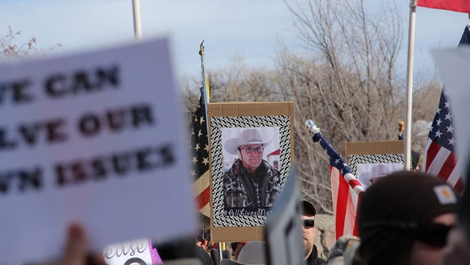 A sign is displayed with the picture of LaVoy Finicum as part of the demonstrations outside the Harney County Courthouse in Burns, Ore., Monday, Feb. 1, 2016. Hundreds gathered to protest and support the armed occupation of a national wildlife preserve.