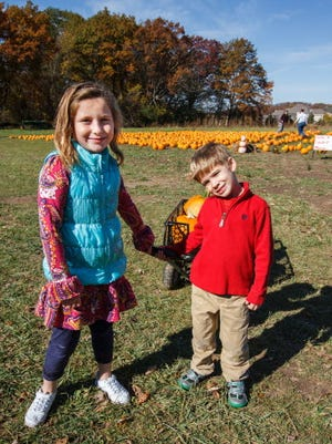 Maya Lauterbach, 7, and her brother Brayden, 5, of Hartland return with a wagon of pumpkins at Shady Maple Farm in Sussex.