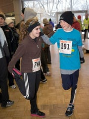 Ava Olson (left), 16, of Delafield, and Alex Dallman, 12, also of Delafield, loosen up their legs before heading to the start line at the Milwaukee County Zoo's Samson Stomp & Romp.