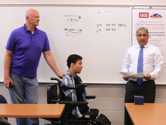Gabe Adams, center, receives the Yes I Can Award for Self-Advocacy from Suraj Syal of the Utah Council for Exceptional Children, right, Wednesday at Dixie High School in St. George as Gabe's father, Ron Adams, listens.