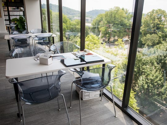 Communal workspaces were placed alongside the floor-to-ceiling windows inside McCarty Holsaple McCarty's downtown Knoxville office.