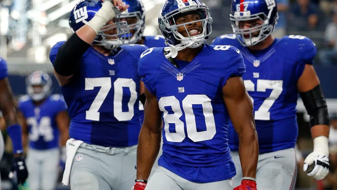 New York Giants center Weston Richburg (70), Victor Cruz (80) and Justin Pugh (67) celebrate a touchdown catch by Victor Cruz (80) in the second half of an NFL football game against the Dallas Cowboys on Sunday Sept. 11, 2016, in Arlington, Texas.
