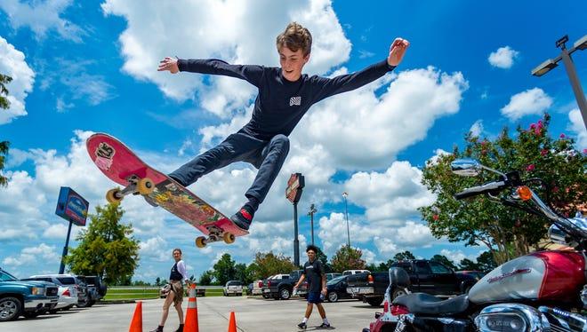 Caden Hudson getting some air jumping over a motorcycle at the Skateboard Park Fundraiser at Cajun Harley Davidson. Saturday, July 14, 2018.