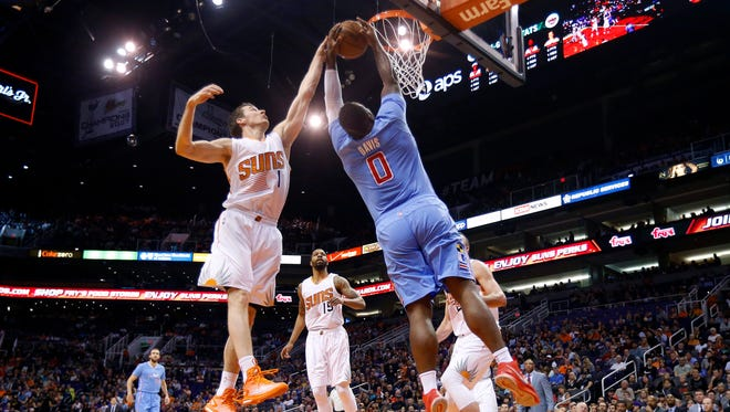 Phoenix Suns' Goran Dragic (1), of Slovenia, gets a hand on the ball that Los Angeles Clippers' Glen Davis (0) tries to dunk as Suns' Marcus Morris (15) looks on during the first half of an NBA basketball game Sunday, Jan. 25, 2015, in Phoenix. (AP Photo/Ross D. Franklin)