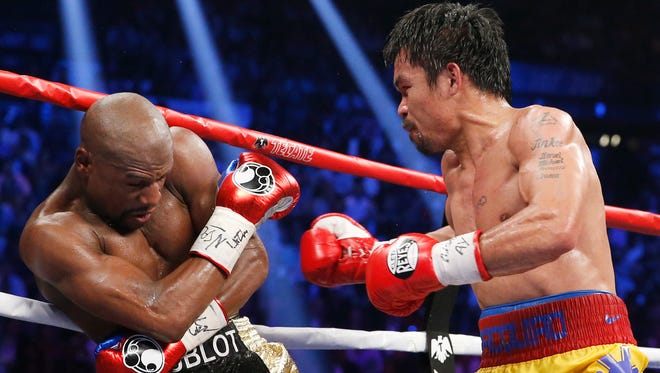 Manny Pacquiao, from the Philippines, right, trades blows with Floyd Mayweather Jr., during their welterweight title fight on Saturday, May 2, 2015 in Las Vegas.
