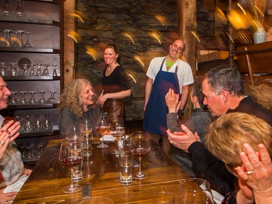 Server Jenna Brauel, left center, and chef de cuisine Nick Cavalli receive applause after presenting a three-course dinner at Hen of the Wood in Waterbury on Thursday, March 31, 2016.