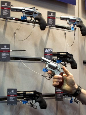 In this April 2014 file photo, a convention goer hefts a Smith & Wesson handgun at the 143rd NRA Annual Meetings and Exhibits at the Indiana Convention Center in Indianapolis.