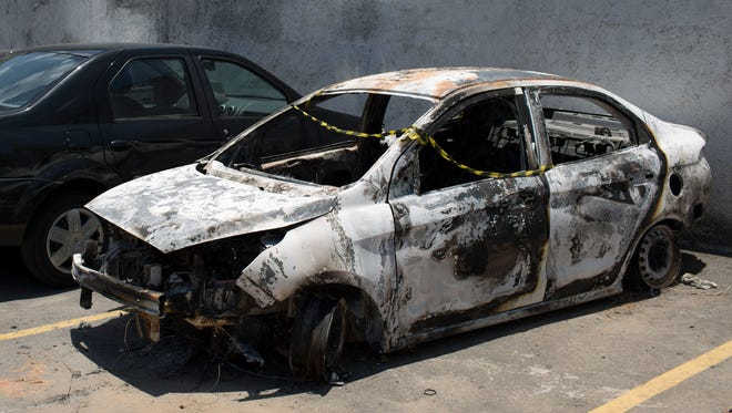 A burned car sits in the parking lot of the police station in Belford Roxo, Brazil, Friday, Dec. 30, 2016. This burned vehicle, matching the description of the car rented by Greece's ambassador to Brazil Kyriakos Amiridis, was found with a body inside it in Nova Iguacu, but forensics experts have not yet identified the dead person.