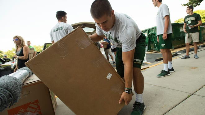 CSU football player Adam Prentice helps new students move into their dorm rooms last week. Prentice tore an ACL in practice Thursday and will miss the 2016 season, coach Mike Bobo said Friday.