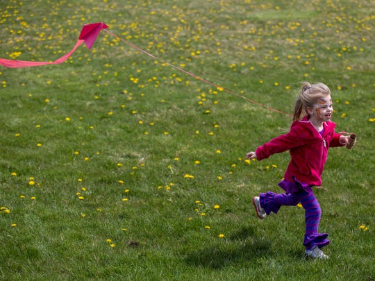 Hailey Higgins, 4, of Algonac, runs with a kite during the Community Kite Day Saturday, April 30, 2016, at Pointe Tremble Early Childhood Center in Algonac.
