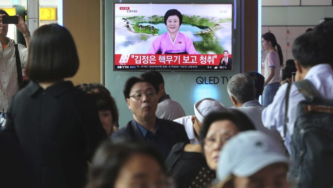 People watch a TV news program at the Seoul Railway Station in Seoul, showing North Korea's announcement that it conducted an underground hydrogen bomb test.