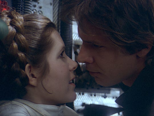 Carrie Fisher (L) as Princess Leia and Harrison Ford