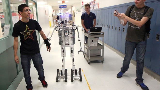 Millville Senior High School students Yamail Walker (left), 17, a junior, Nathan Heaton, 16, a sophomore, and Kyle Permui, 16, a sophomore, walk with Mr. Robot at a technology showcase.