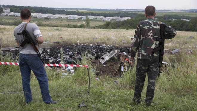 Pro-Russian fighters guard the site of a crashed Malaysia Airlines passenger jet near the village of Rozsypne, Ukraine,  Friday.