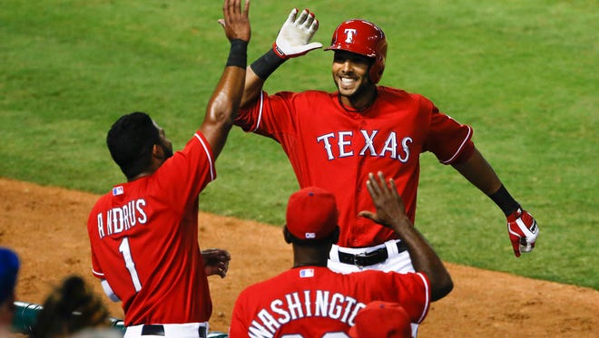 Texas Rangers right fielder Alex Rios is congratulated by shortstop Elvis Andrus and manager Ron Washington after his solo home run against the Houston Astros.