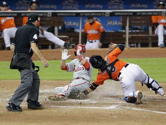 Philadelphia Phillies' Chase Utley slides into home to score on a single by Ryan Howard as Miami Marlins catcher Jhonatan Solano attempts the tag during the seventh inning Sunday.