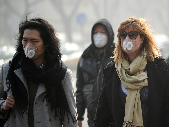 People protect themselves against heavy air pollution on Jan. 16 in Beijing.  China's capital was shrouded in thick smog, cutting visibility as small particulate pollution climbed to more than 24 times the recommended safety level.