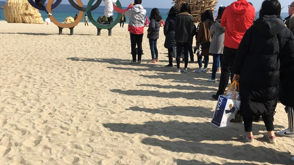 """In this Friday, Feb. 23, 2018 photo, Olympic fans wait in line at Gyeongpo Beach in Gangneung, South Korea,  to take their photo with the Olympic rings. While some days, it seemed like fans were more excited about the two giant, tented """"superstore"""" gift shops than they were about the actual games, others opted for pictures with the waterfront rings as it was the cheapest - and most popular - souvenir at the games.  (AP Photo/Scott Mayerowitz)"""