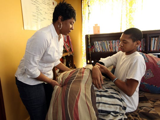 Lashaunda Green adjusts pillows for her son Michael Green II, 12, who is home from the hospital, recuperating after being shot while playing basketball in Detroit.