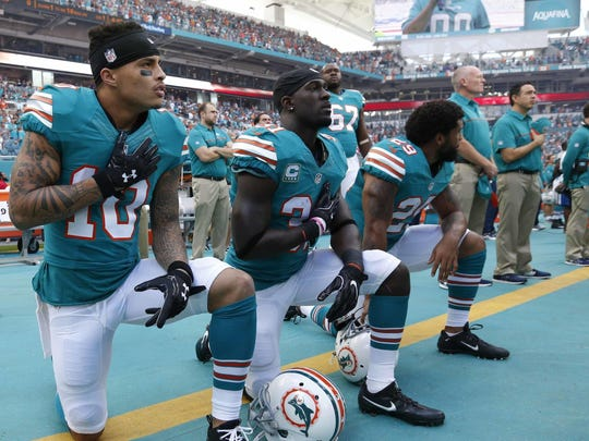 In this Sunday, Oct. 23, 2016, file photo, Miami Dolphins wide receiver Kenny Stills (10), free safety Michael Thomas (31) and defensive back Chris Culliver (29) kneel during the National Anthem before the first half of an NFL football game against the Buffalo Bills. Miami Dolphins players who protest on the field during the national anthem this season could be suspended for up to four games under a new team policy issued to players this week. The policy obtained by The Associated Press on Thursday, July 19, 2018 classifies anthem protests as conduct detrimental to the club, punishable by suspension without pay, a fine or both.